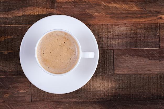 Прямо над крышкой кофе капучино или латте на деревянный стол
