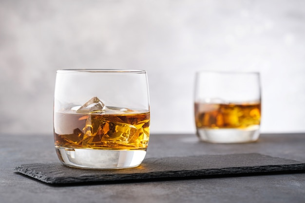 Крупным планом виски с кубиками льда на сером фоне