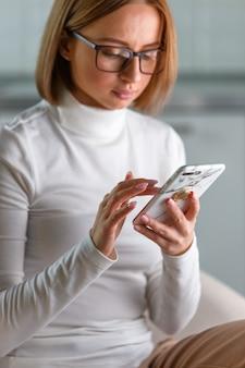 Серьезная деловая женщина носит белую водолазку и очки с помощью современного смартфона, просматривает интернет, покупает товары онлайн