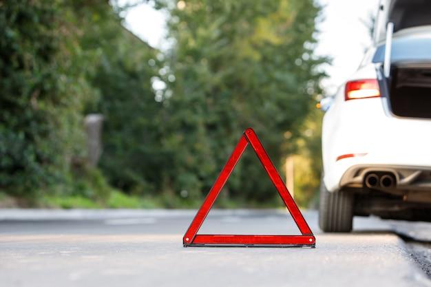 赤い警告トライアングルサインシンボルと道端で壊れた白い車のクローズアップ