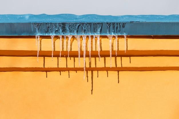 黄色の壁の上の屋根につららが溶ける