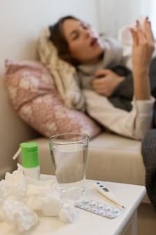 Затуманенное больная женщина, лежа на диване, чихая в носовой платок