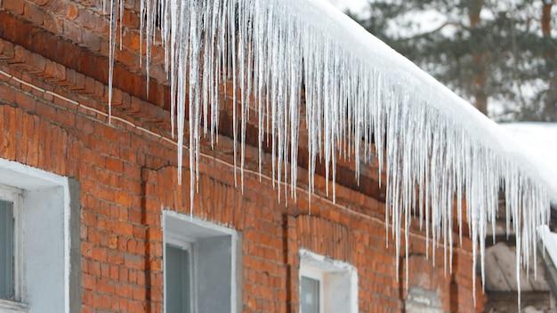 赤レンガの壁で屋根からぶら下がっている氷の鍾乳石