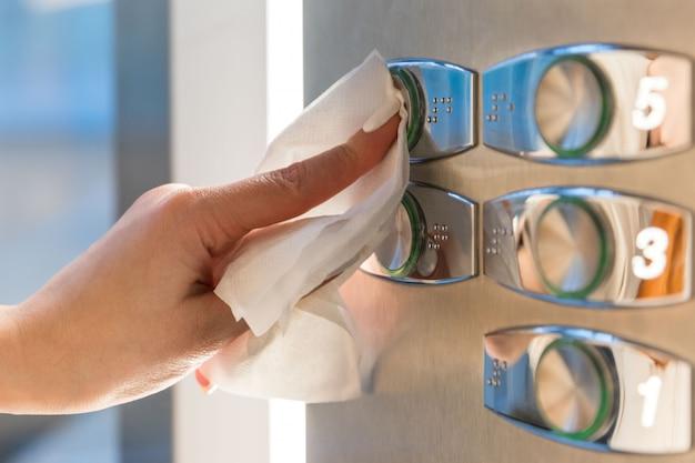 Женщина указательным пальцем, нажав кнопку в лифте через салфетку