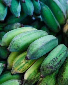 デザートやベジタリアン料理を作るために、熱帯の熟した緑のバナナのクローズアップ。タイの果物市場。