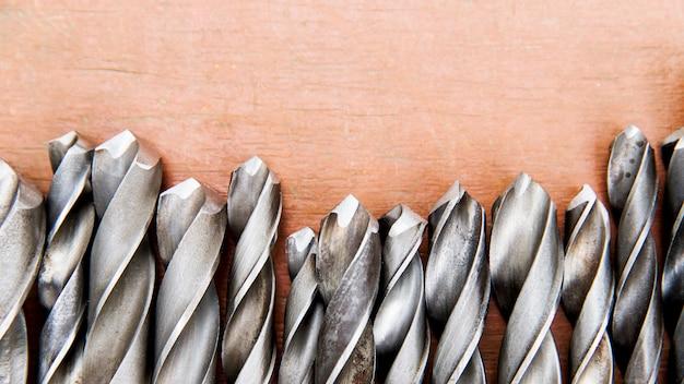 Набор старых различных спиральных сверл с различными размерами на деревянном фоне, крупным планом, вид сверху