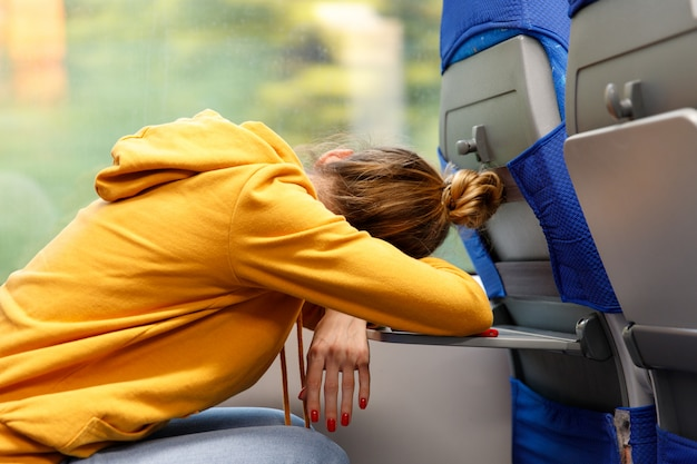座席に座って公共交通機関の折りたたみテーブルで寝ているオレンジ色のパーカーの女性