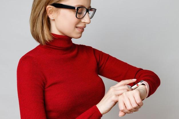 赤いタートルネックで自信を持ってスタイリッシュなビジネスウーマン、光学めがねを着用、触れたり、設定したり、手首にスマートウォッチを使用したり
