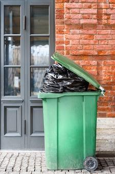 Открыт большой зеленый пластиковый мусорный бак с полными мешками для мусора. утилизация отходов