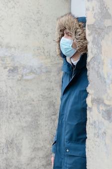 Человек с капюшоном в защитной одноразовой маске от передаваемого коронавируса
