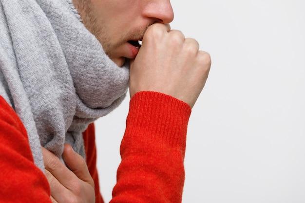 Нездоровый человек в оранжевом свитере страдает от кашля от простуды, гриппа