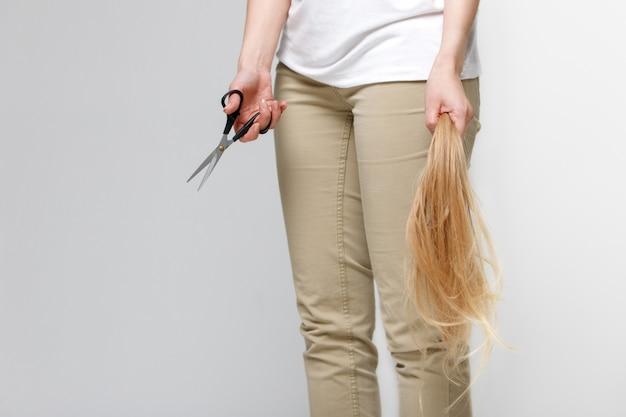 Женщина держит ее бывшие длинные волосы после стрижки и ножницы в руке