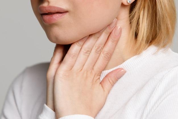 Женщина страдает от проблем с горлом, держась за руки на ее лимфатических узлах