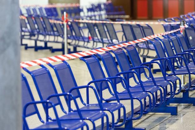 椅子に伸ばした保護赤いテープ。コロナウイルスの大流行の間、人々を感染から守るために公の席に座ることは禁止されています。