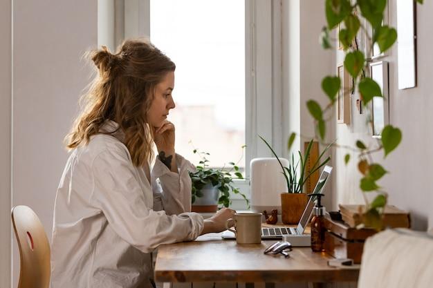 自己分離中にホームオフィスからコンピューターに取り組んでいる女性フリーランサー/デザイナー。リモートワーク、在宅勤務、距離の仕事。