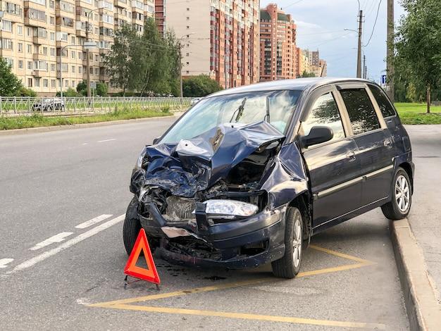 街での自動車事故。車のボンネット、ヘッドライト、フロントバンパー、エンジンに事故後の大きな損傷