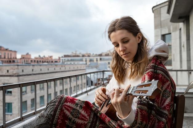 Молодой кавказской битник / хиппи женщина в повседневной одежде играет на гавайской гитаре, поет песню на гавайской гитаре в доме на террасе.