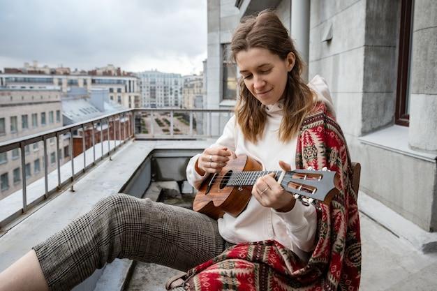 Кавказский хипстер / хиппи женщина в повседневной одежде играет на гавайской гитаре, поет песню на гавайской гитаре во время самоизоляции в доме на террасе.
