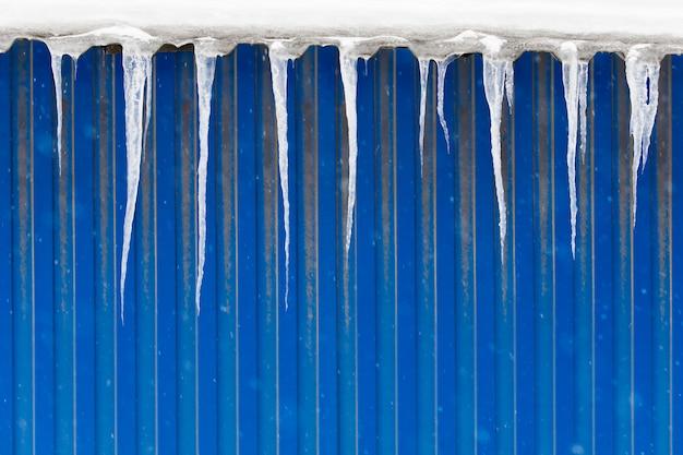 Сосульки свисают с крыши здания с металлической стеной синего цвета