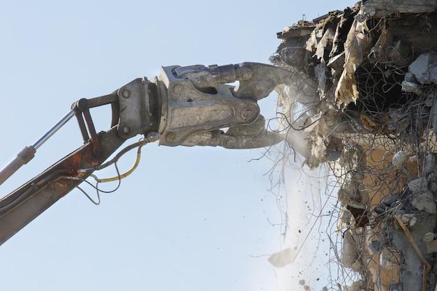 油圧ショベル/油圧カッタークレーンによるコンクリートのアパートの建物の解体。新しい建物の場所を作る。