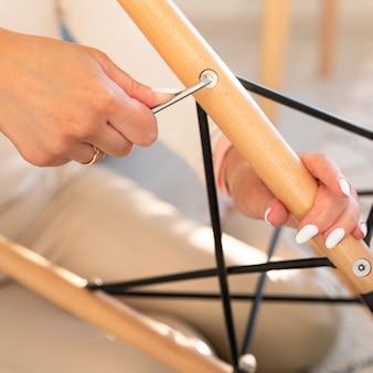 Женщина самостоятельно собирает кресло, затягивая болты с помощью шестигранного гаечного ключа для мебели