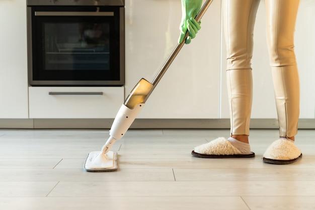 マイクロファイバースプレーモップパッドと詰め替えボトルを使用して、アパートの床を拭くゴム手袋の女性