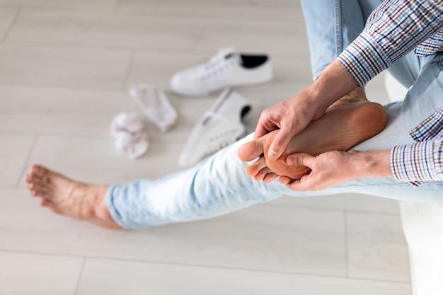 不快な靴が原因で、長い歩行の後に痛みを和らげるために、自分の足にマッサージをする男性の手。