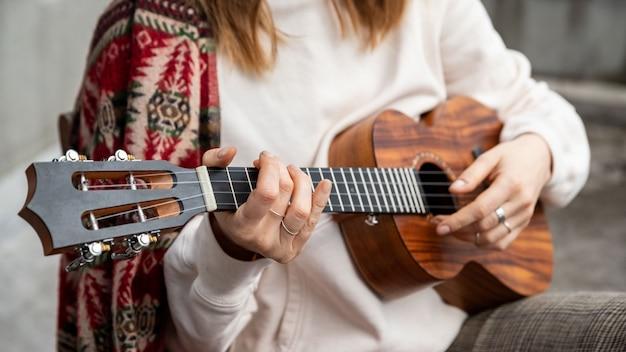 Женщина играет на гавайской гитаре, поет песню на винтажной укулеле дома. выборочный фокус