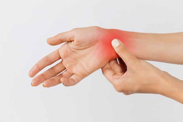 Женщина руки держат ее болезненные запястья, вызванные длительной работой на ноутбуке, окрашены в красный цвет. синдром карпального канала, артрит