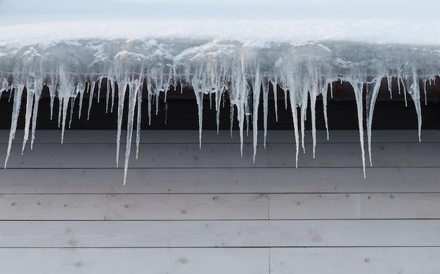 つららで覆われた建物、クローズアップ。屋根、コピースペースからぶら下がっている氷の鍾乳石