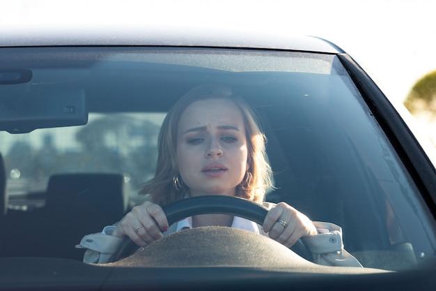Женщина водит свою машину впервые. неопытный водитель в стрессе и растерянности после дтп