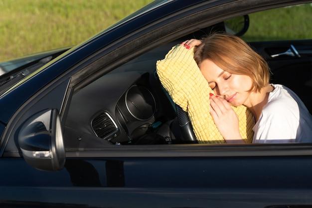 Утомленная молодая женщина водитель спит на подушке на руле, отдыхая после долгих часов за рулем автомобиля.