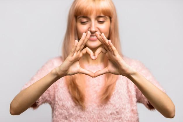 Улыбающаяся молодая женщина, делающая сердечный жест ее пальцами, показывая изолированный символ любви,