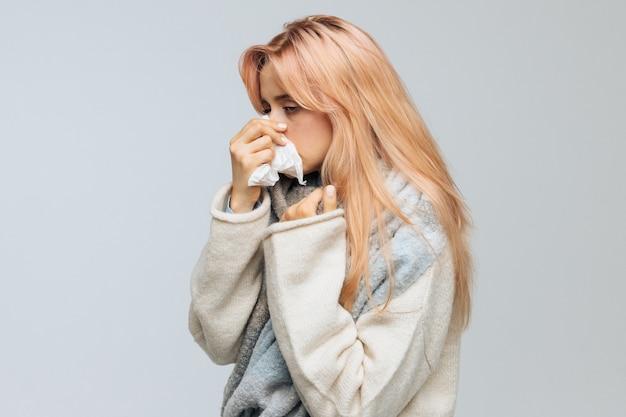 Женщина чихает или использует носовой платок, чтобы вытереть сопли с носа.