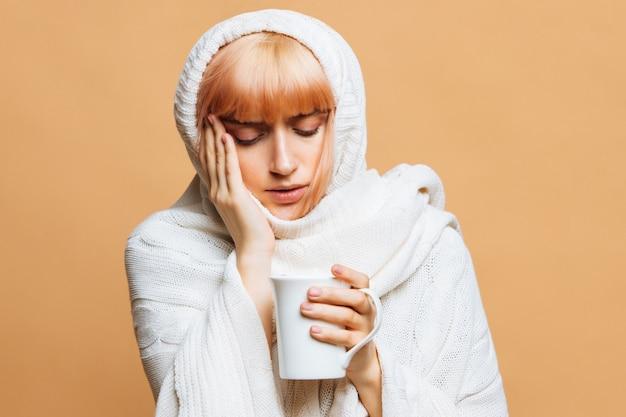 Молодая женщина тепло плед с головной болью, держа чашку горячего чая, касаясь ее виска