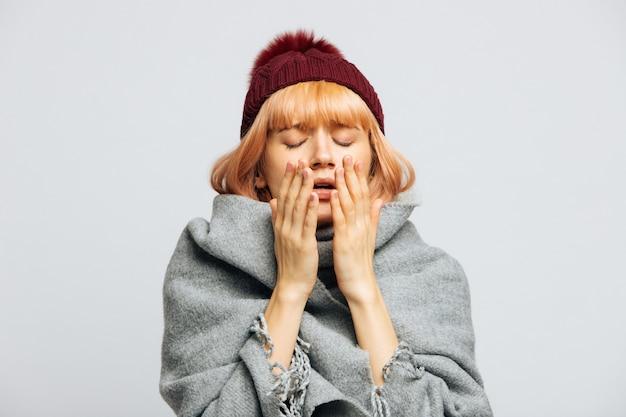 Женщина в красной шляпе, в чихающем теплом шарфе, испытывает симптомы аллергии, простудилась