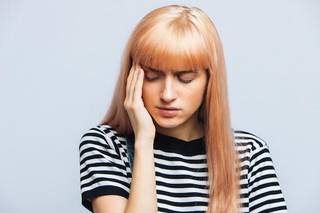 Подросток женщина, имеющая головную боль, держа ее висок, чувствуя давление