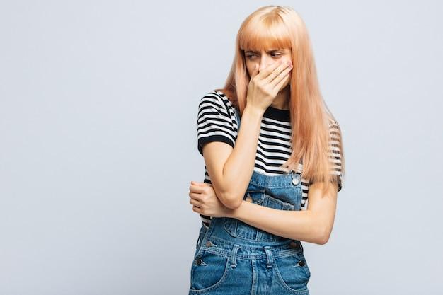 Самка в полосатой футболке прикрывает нос рукой, смотрит на источник аллергии или неприятного запаха