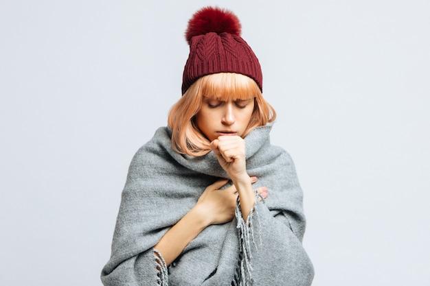 Женщина в красной шляпе, завернутая в теплый шарф, кашляет