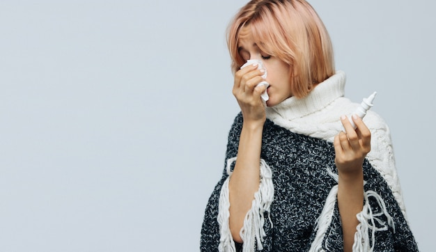 Женщина с бумажной салфеткой чихает, используя назальный спрей, чтобы помочь себе. аллергия, грипп