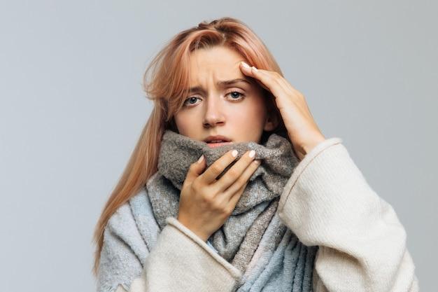暖かいスカーフに包まれたインフルエンザの最初の症状を感じる女性