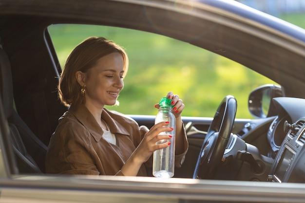 Женщина-водитель пьет воду из бутылки многоразового использования в своей машине, остановилась отдохнуть