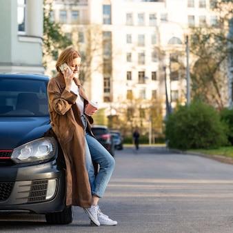彼女の車の近くに立って、電話で話している、コーヒーカップを保持している女性