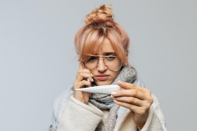 Женщина в очках смотрит на термометр, звонит врачу по телефону.