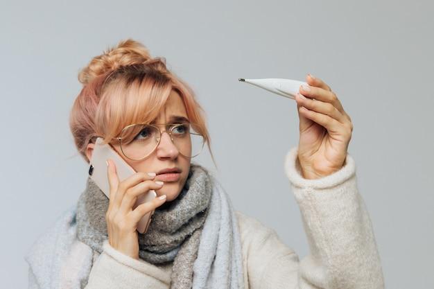 Женщина в очках простудилась, смотрит на градусник, вызывает врача. концепция сезона гриппа