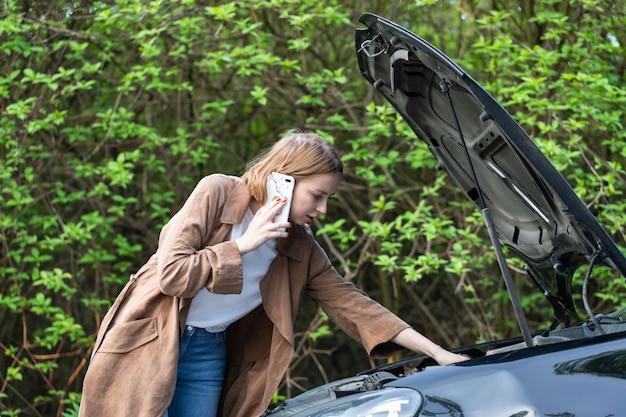 Беспомощная женщина-водитель, зовущая на помощь / помощь, смотрит на сломанную машину, остановилась на обочине.
