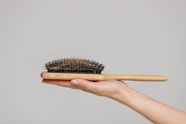 脱毛の問題。失われた髪、サイドビューと櫛ブラシを持つ女性の手のクローズアップ