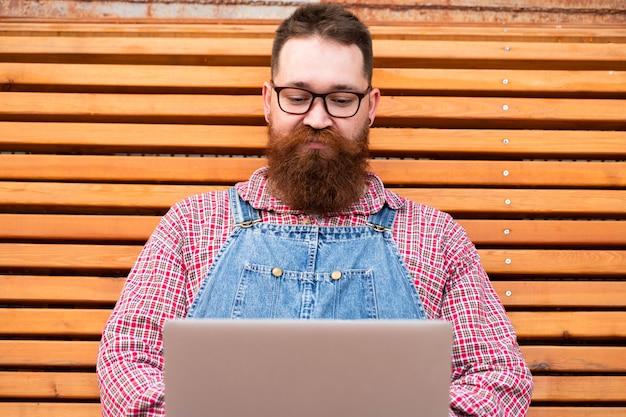 屋外のベンチに座っているラップトップに取り組んでいるジーンズのオーバーオールで深刻な残忍なひげを生やした流行に敏感な男。距離の仕事、遠隔作業。