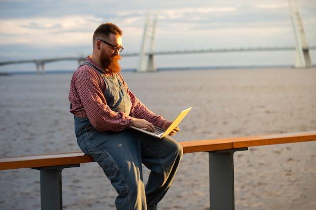屋外の堤防でラップトップに取り組んでいる青いオーバーオールを着ている残忍なひげを生やした男のフリーランサー。距離の仕事