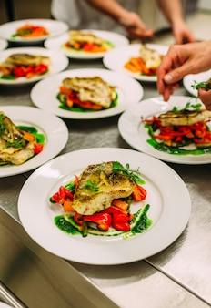 ケータリングのための野菜と魚料理。たくさんのプレート。